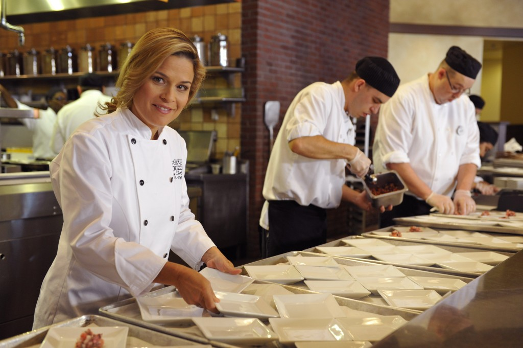 Celebrity chef Cat Cora prepares dishes prior to the grand opening of her first signature restaurant
