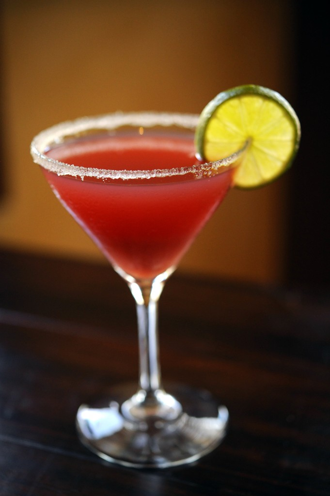 Kouzzina Ouzo-tini featuring Absolut vodka, Metaxa ouzo, pineapple juice, fresh lime juice and pomegranate served in a sugar-rimmed martini glass shaken and served tableside