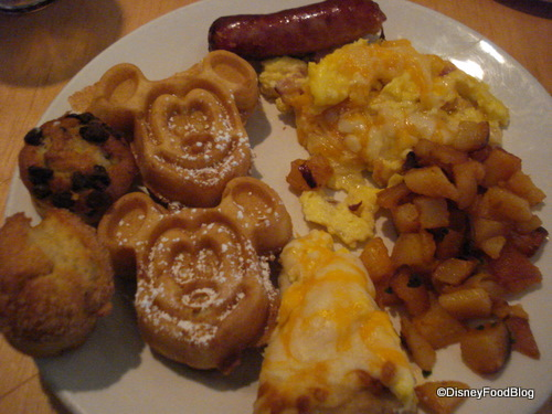 Food plate all ready to go: mickey waffles, eggs, breakfast pizza, homefries, muffins, and sausage