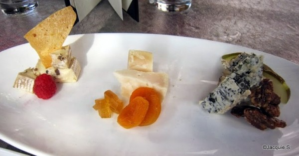 Cheese Plate, featuring Champignon Brie, Midnight Moon Goat, and Flora Nelle Blue with Raisins on the vine, Pear Jelly, Spiced Pecans, and Crostini
