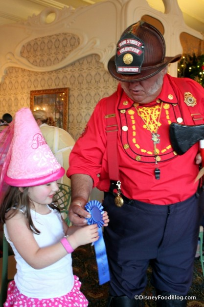 Main Street Fire Chief Gives the Mayor of the Day Badge to a Young Guest