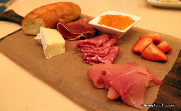 Assorted Cured Meats and Cheeses -- alpine-smoked ham, serrano ham, sopressata, and cheese served with marmalade, fresh fruit, and toasted baguette