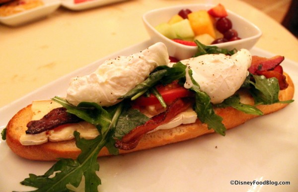 Open-Face Bacon and Egg Sandwich with poached eggs, applewood bacon, and brie cheese on a toasted baguette served with fresh fruit