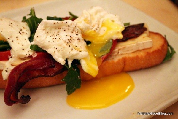 Open-Face Bacon and Egg Sandwich with poached eggs, applewood bacon, and brie cheese on a toasted baguette